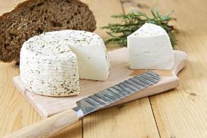 queijo branco, verduras e pão em um fundo de madeira foto