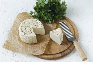 queijo branco em uma placa de madeira em um fundo branco com verduras foto