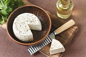 queijo branco em uma placa de madeira com azeite em um fundo marrom foto