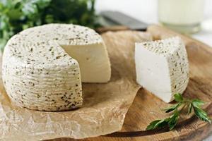 queijo branco em uma placa de madeira em um fundo branco foto