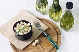 queijo branco em uma placa de madeira com azeite em um fundo branco foto