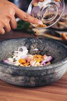 uma pessoa servindo especiarias em uma tigela cinza cheia de anéis de cebola