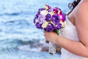 noiva segurando buquê de casamento em uma praia tropical