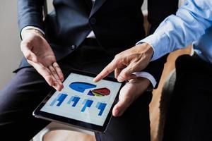 duas pessoas apontam para tabelas e gráficos em um tablet foto
