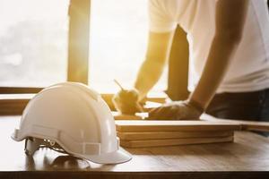 trabalhador da construção civil trabalhando na madeira ao lado do capacete e da janela foto