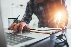 close-up de um homem trabalhando em um laptop ao lado da janela foto