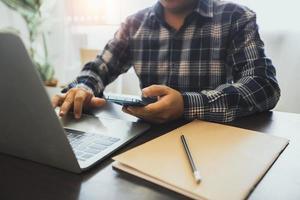 close-up de um homem trabalhando em um laptop e um celular ao lado da janela foto