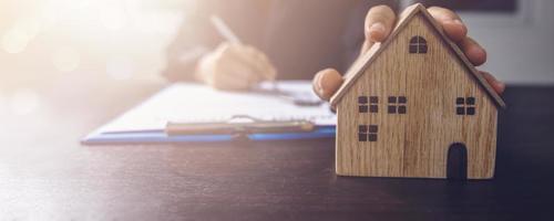 pessoa escrevendo no papel e segurando uma casa modelo