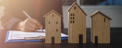 pessoa escrevendo no papel ao lado de três casas modelo