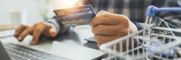 homem segurando um cartão de crédito e trabalhando em um laptop foto