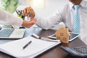 empresário entrega uma chave para uma pessoa ao lado do laptop, do contrato e da casa modelo foto