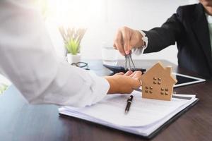 empresário entregando as chaves para uma pessoa ao lado de um tablet, uma casa modelo e um contrato foto