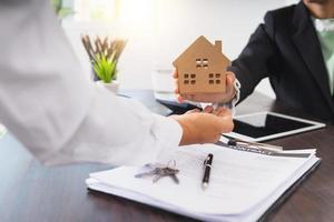 empresário entregando modelo de casa a uma pessoa sobre um contrato, chaves e tablet foto