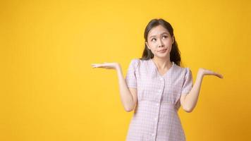 mulher asiática gesticulando com as palmas das mãos para cima em fundo amarelo foto