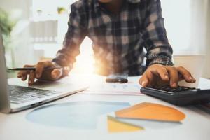 homem trabalhando no laptop e na calculadora ao lado de papéis de tabelas e gráficos foto