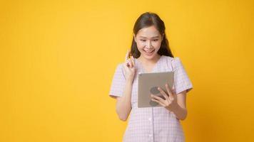 mulher asiática sorrindo e olhando para um tablet em fundo amarelo foto