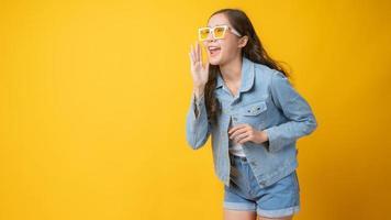 mulher asiática sorrindo e gesticulando com a mão aberta ao lado da boca em fundo amarelo foto