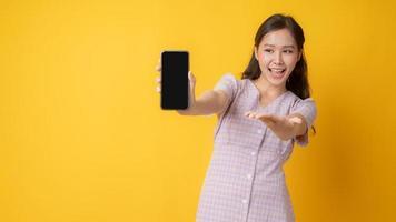 mulher asiática gesticulando em direção a um celular preto em branco sobre fundo amarelo foto
