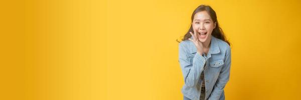 mulher asiática sorrindo e gesticulando com a mão ao lado da boca em fundo amarelo foto