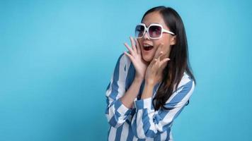 mulher asiática com óculos de sol brancos com as mãos perto da boca gesticulando em direção ao espaço de cópia sobre fundo azul foto