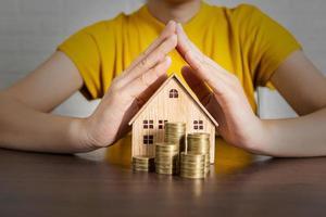 pessoa com casa modelo e pilhas de moedas