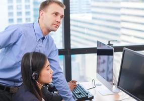 funcionários de call center em grupo trabalhando on-line em um escritório moderno foto