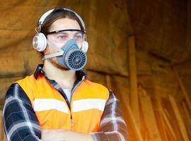 retrato de um jovem carpinteiro usando luvas de segurança e protetores de ouvido à prova de som foto