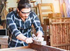 um jovem e bonito carpinteiro está processando madeira para móveis foto