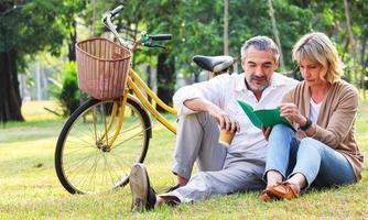 casal feliz sentado no parque com uma bicicleta foto