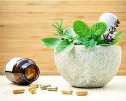 ervas frescas em um pilão com pílulas de ervas