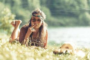 menina hippie muito livre fumando na grama, efeito de foto de efeito vintage