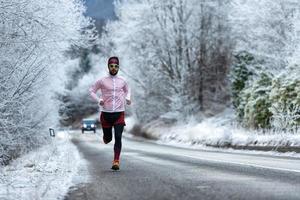 jovem corredor em uma estrada gelada nos Alpes