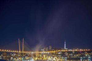 paisagem noturna da ponte dourada em vladivostok, rússia foto