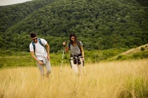 casal sorridente caminhando com mochilas pelas colinas verdes foto