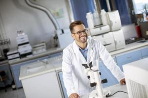 jovem cientista vestindo jaleco branco trabalhando com microscópio binocular no laboratório de ciências materiais foto