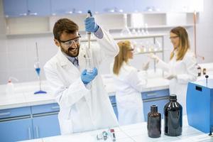 jovens pesquisadores em roupas de trabalho de proteção em pé no laboratório e analisando frasco com líquido foto