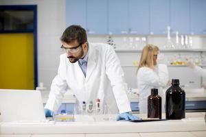 pesquisador de jaleco branco trabalhando em um laptop enquanto está sentado no laboratório foto
