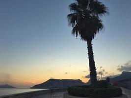 praia mediterrânea sem pessoas ao pôr do sol em calpe, alicante foto