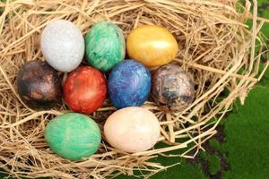 cesta de palha com ovos de páscoa em um fundo de grama