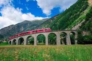 swiss mountain train bernina express atravessa a ponte no cir