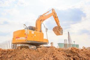 máquina escavadeira em um canteiro de obras contra o fundo do céu azul foto