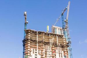 guindastes de construção industrial e edifício em um fundo de céu azul lindo
