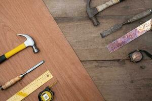 vista superior de um velho martelo, formão e fita métrica em um conjunto de novas ferramentas manuais em uma bancada de madeira foto