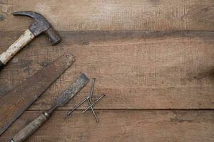 vista superior de um velho martelo, formão e lima em uma antiga bancada de madeira foto