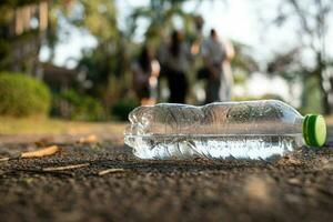 close-up de uma garrafa de água de plástico transparente com uma tampa verde na estrada no parque, com pedestres andando no fundo desfocado foto
