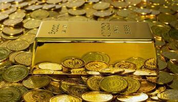 close-up de uma barra de ouro brilhante de 1 kg em uma pilha de moedas de ouro