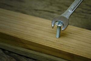close-up de uma chave de fenda aparafusando uma porca em uma prancha de madeira, sem usar o conceito de ferramenta certa