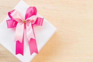 laço de fita rosa em uma caixa de presente branca em um fundo de madeira foto