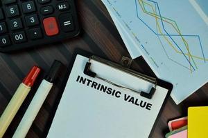 valor intrínseco escrito na papelada isolada na mesa de madeira
