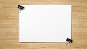clipe de papel preto isolado em papel branco em fundo de madeira foto
